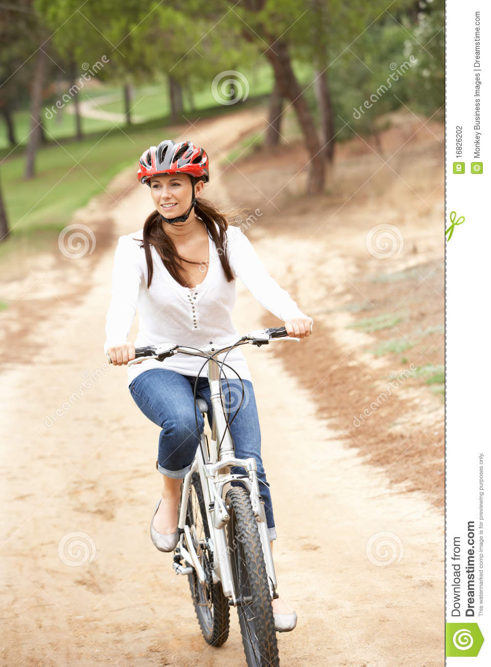 Woman Riding Bicycle In Park Stock Photo