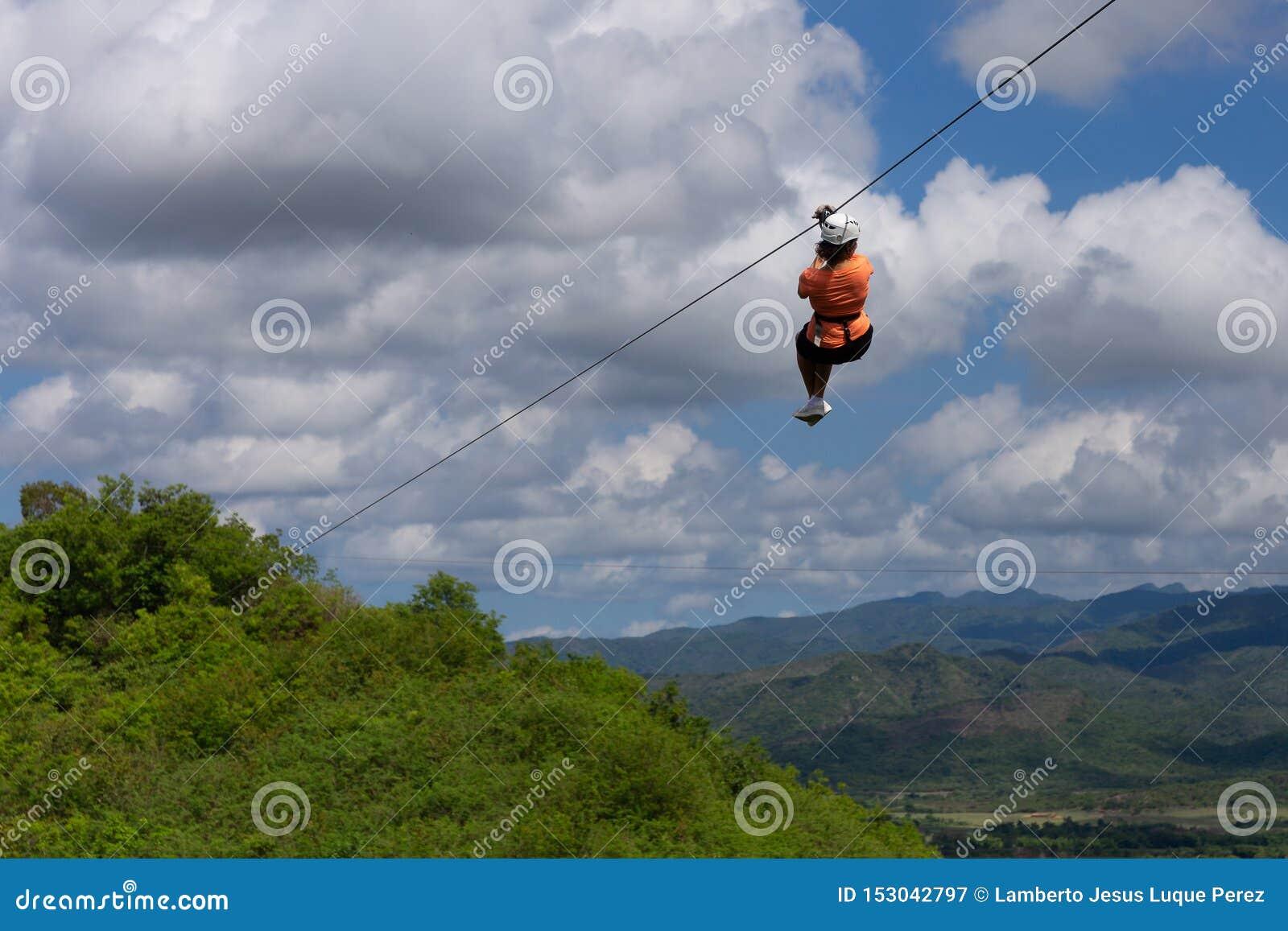Woman riding in zip line in the Valley of Sugar Mills in Trinidad Cuba