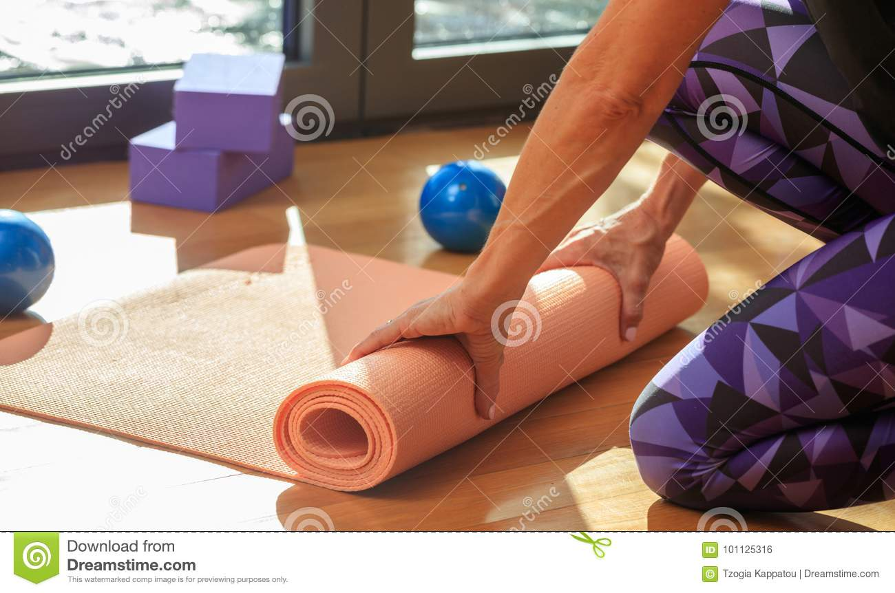 Woman Rolling A Yoga Mat On Wooden Floor Stock Photo