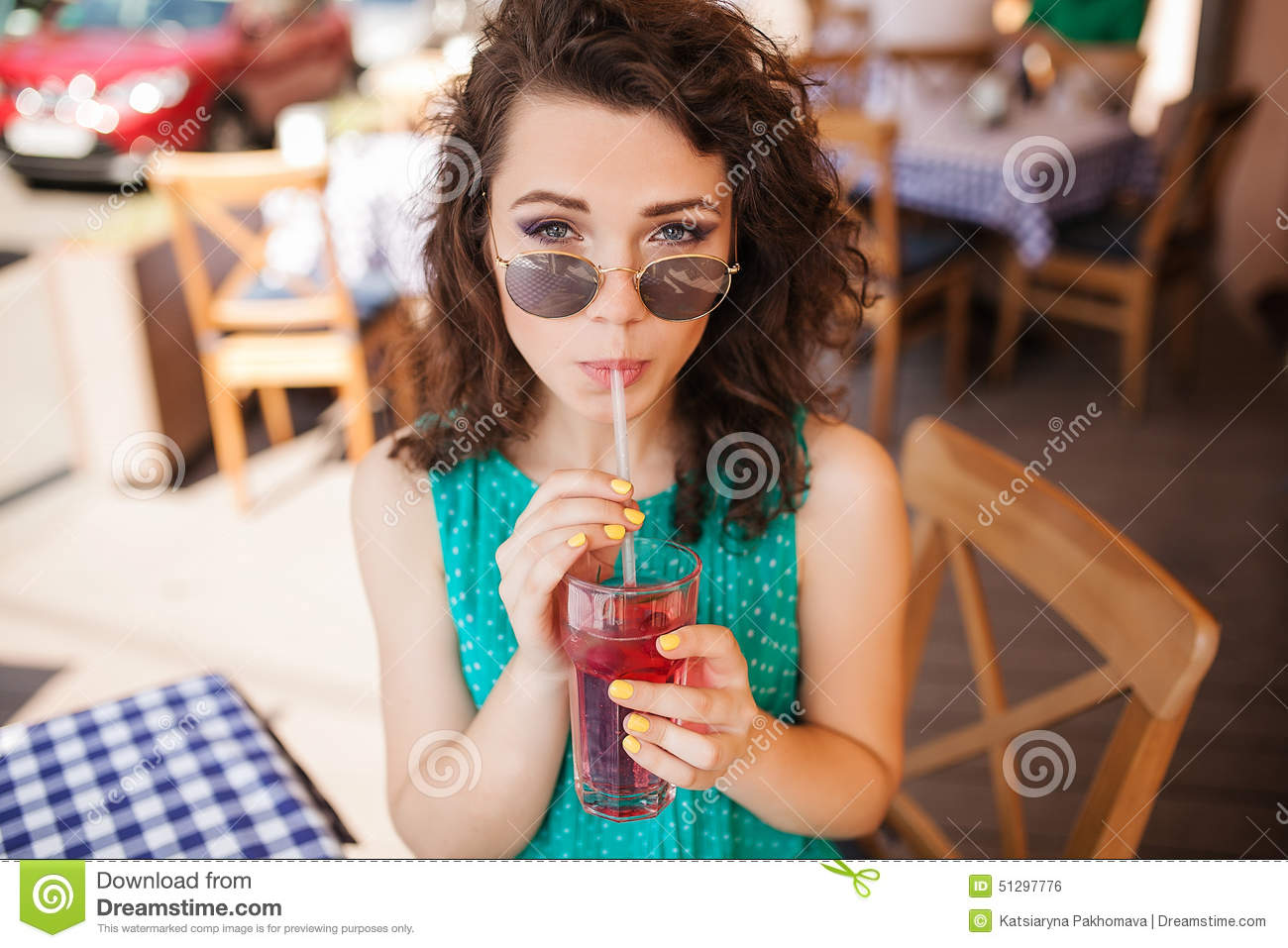 Woman in round sunglasses with cocktail at cafe terrace having fun