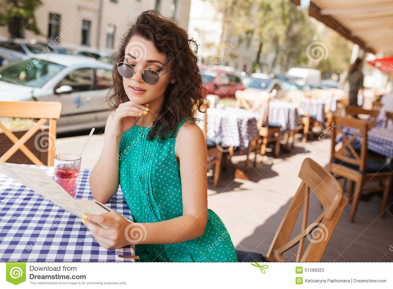 Woman in round sunglasses with cocktail making order at cafe