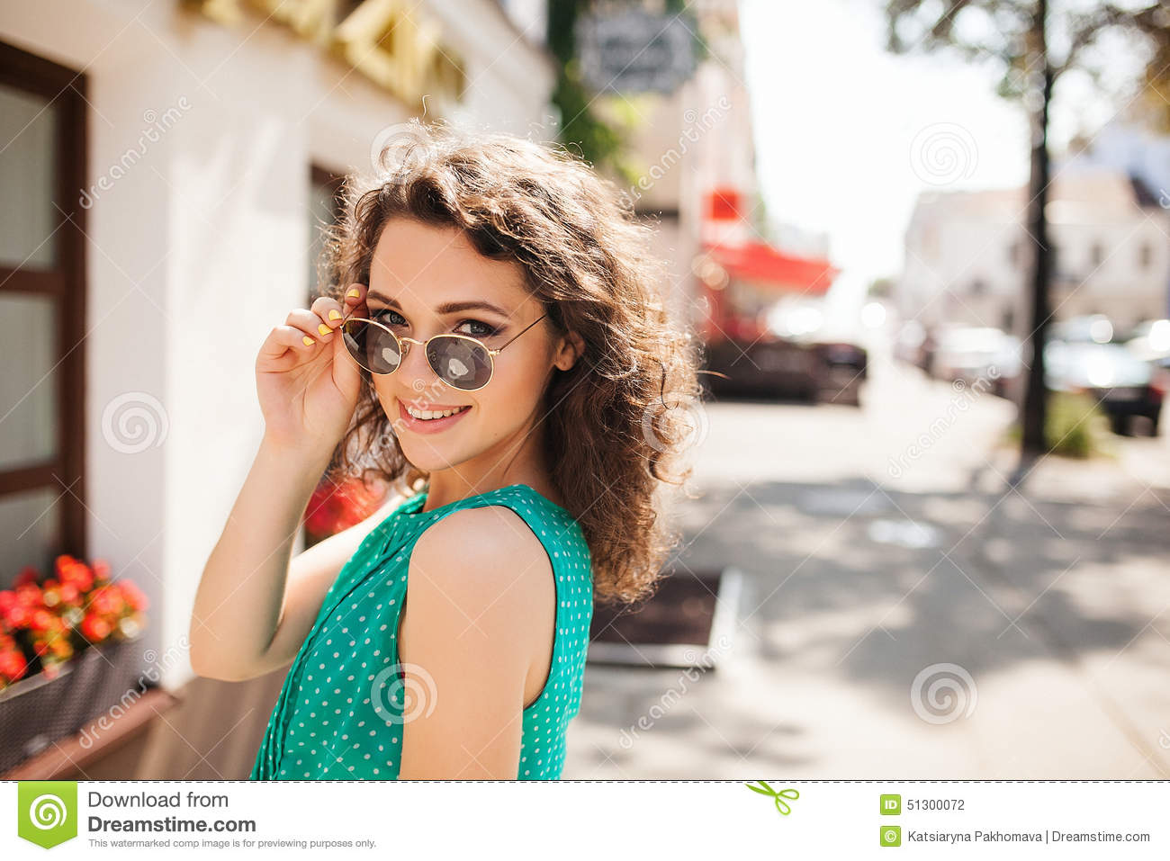 Woman in round sunglasses smiling over shoulder in city street