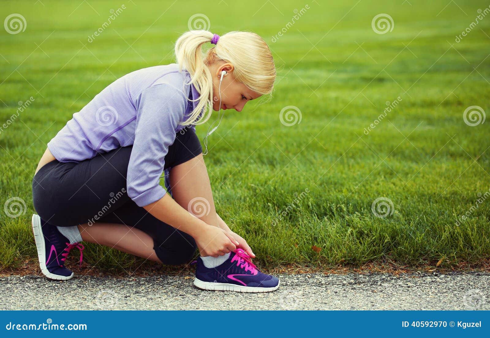 Woman Runner Tying Running Shoes. Blonde Girl Over Grass ...