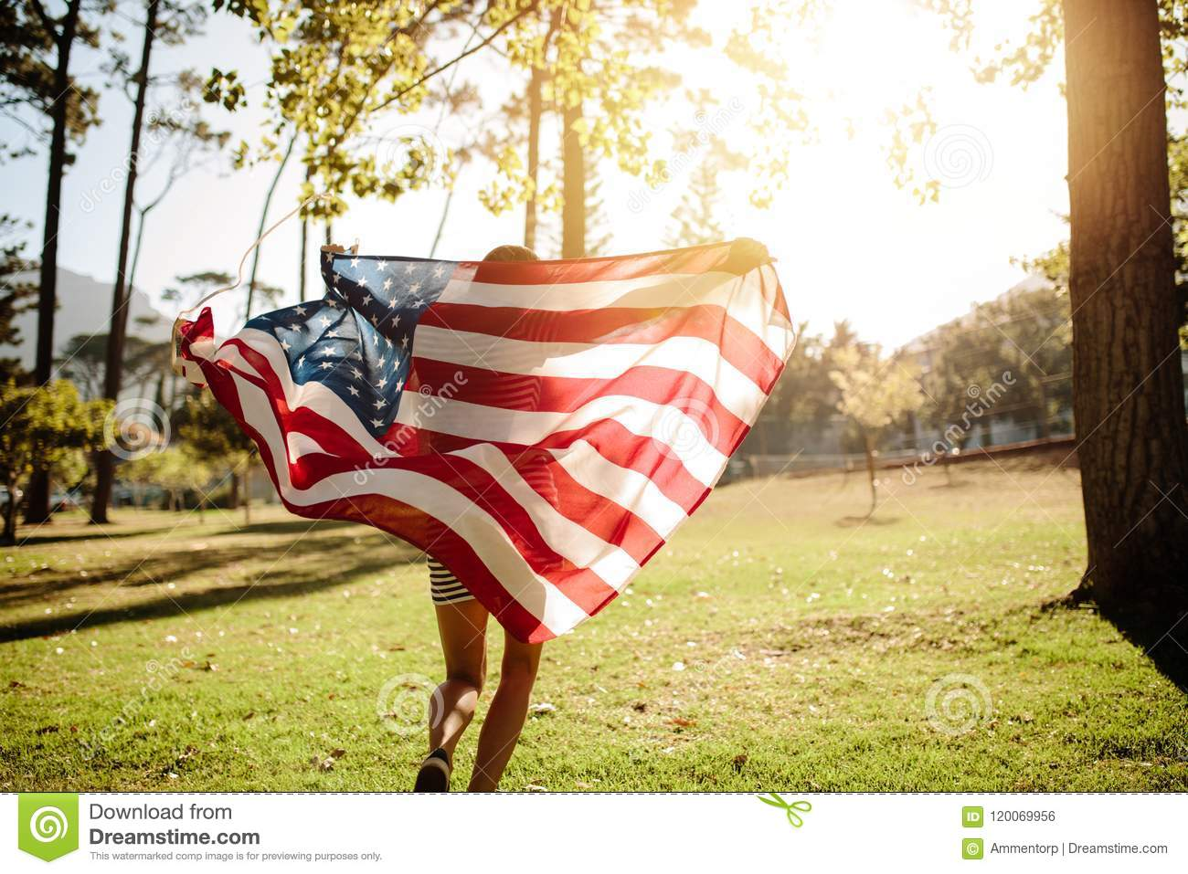 Woman running with american flag in park