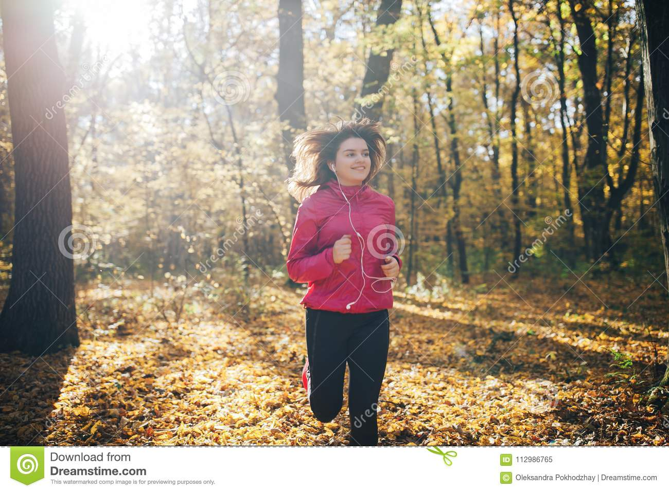 Woman running during autumn morning forest