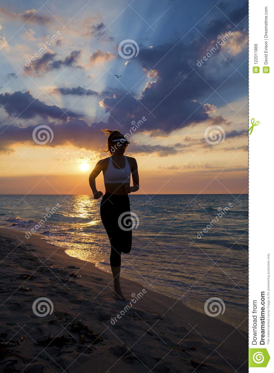 Woman running on the beach during sunset.
