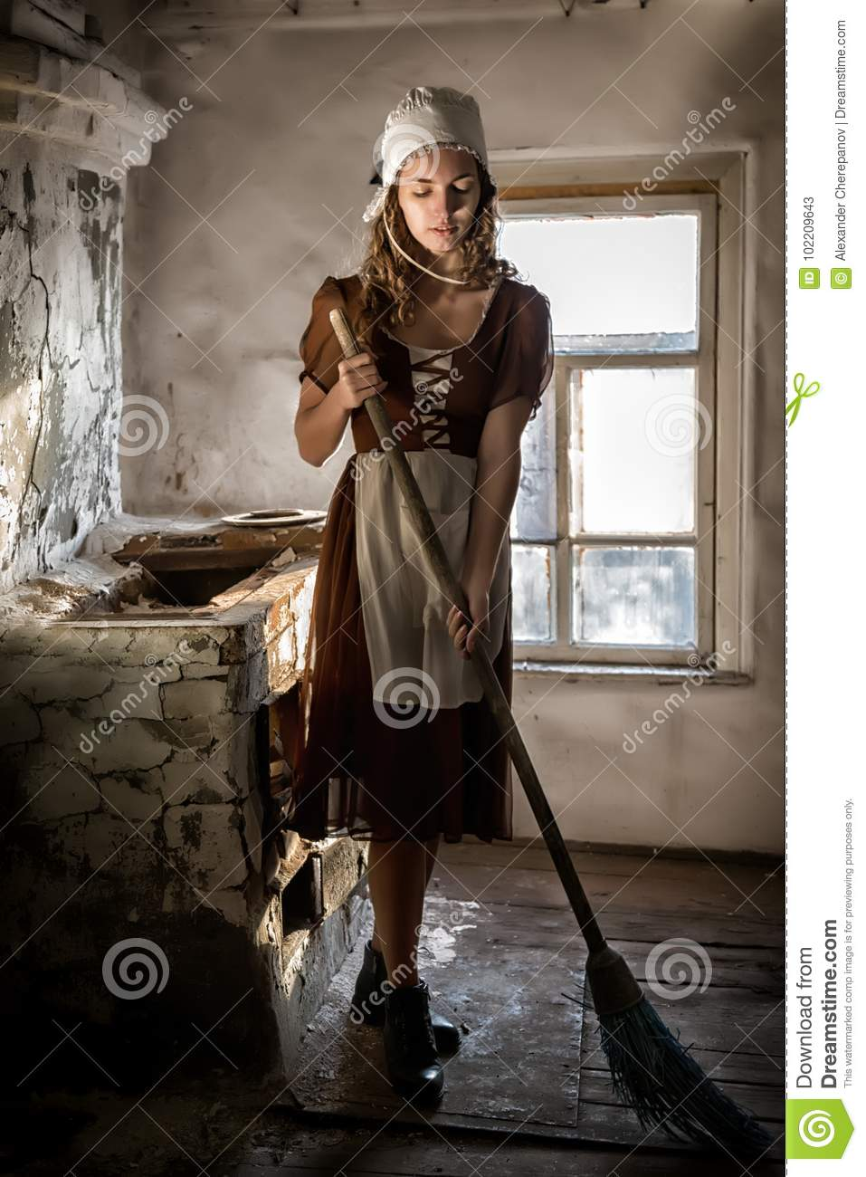 Woman in a rustic dress sweeps the wooden floor in the kitchen