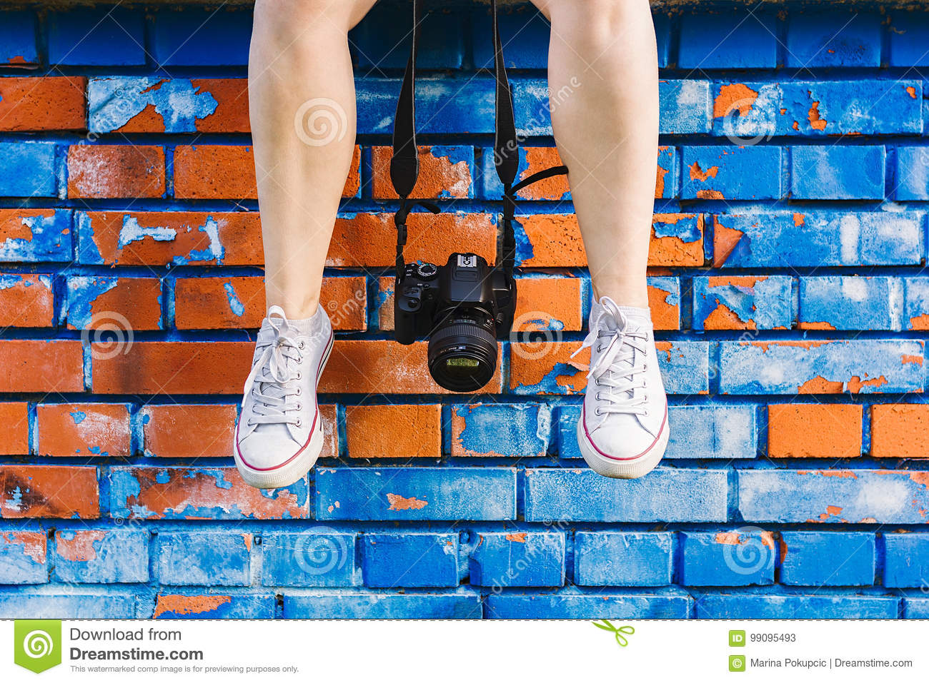 Woman`s feet and photo camera dangling in front brick wall