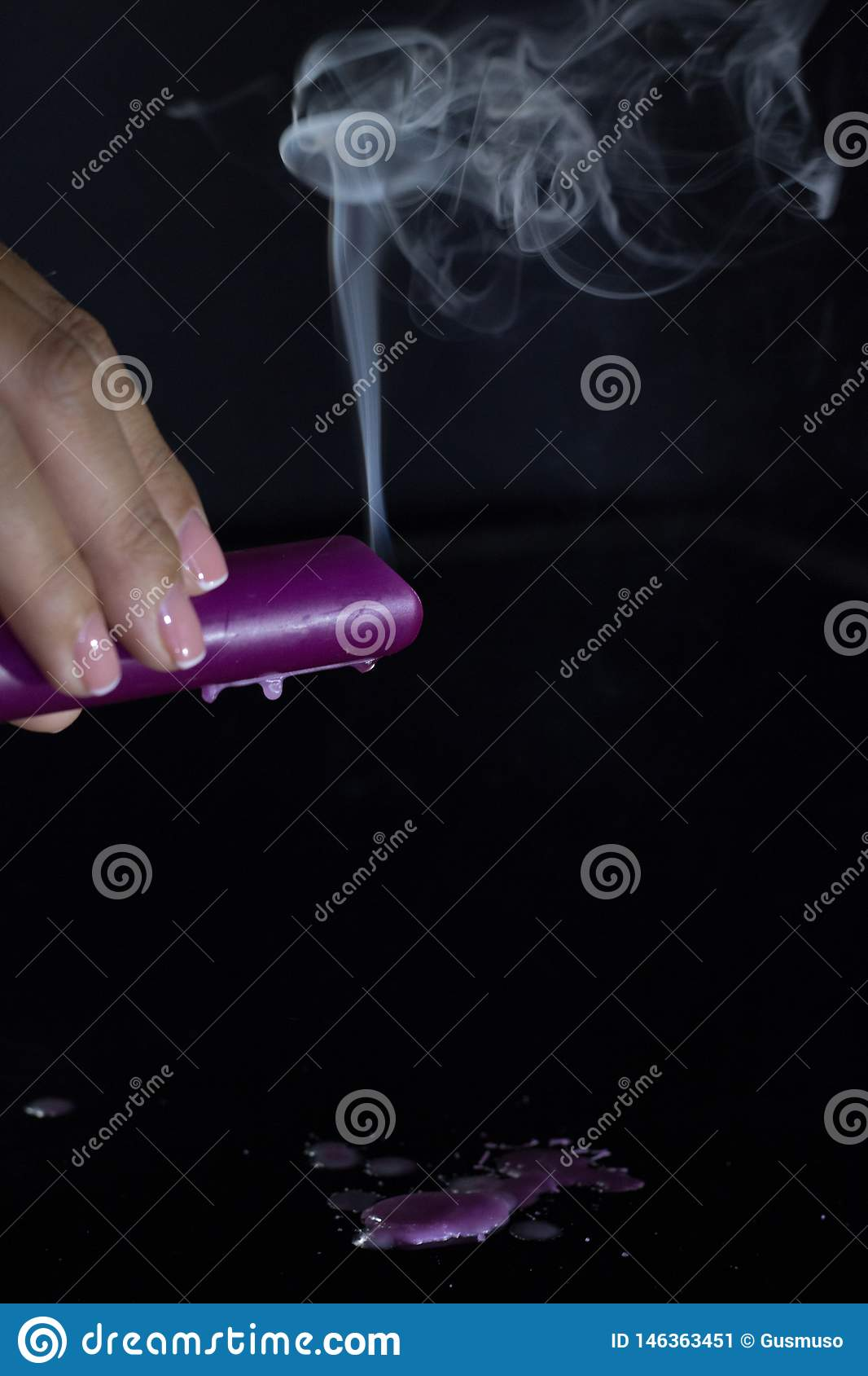 A woman`s hand with a beautiful silver ring holds a smoking purple candle