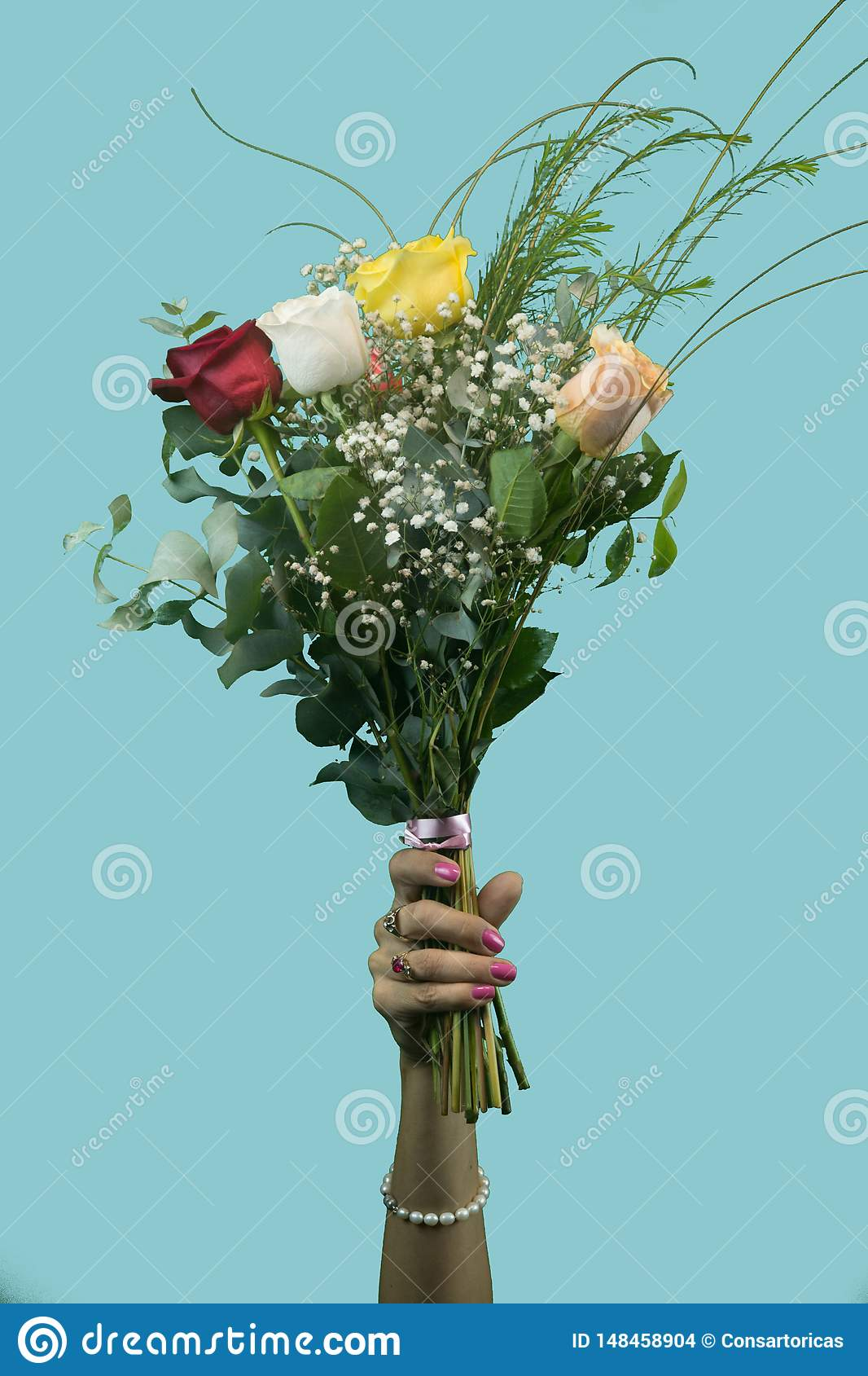 Woman`s hand holding a bouquet of roses