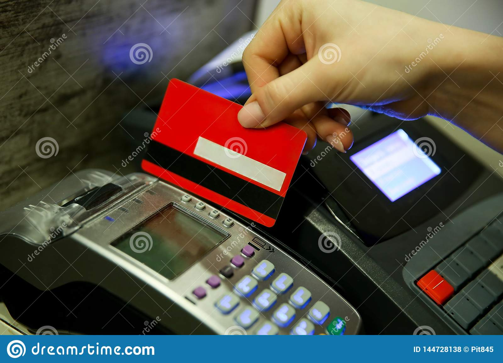 The woman`s hand pays for the purchase with a card with a magnetic stripe.