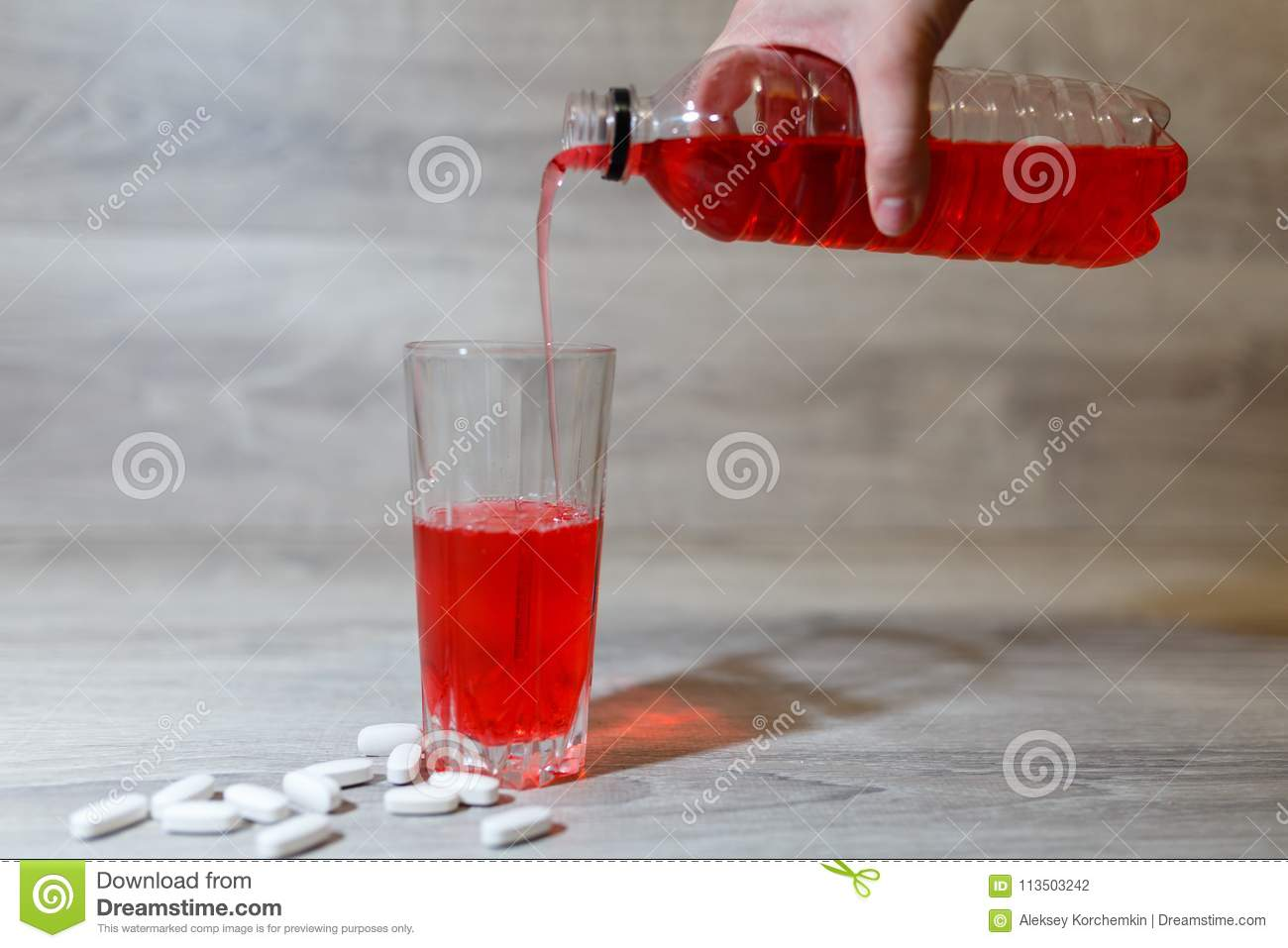 A Woman's Hand Pours A Red Sports Drink Or Lemonade Into A Glass Cup