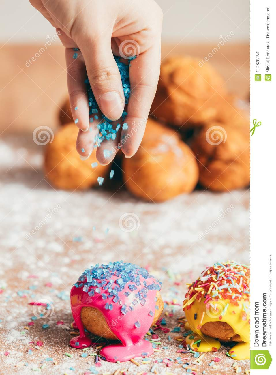 Woman sprinkling sugar strands on doughnuts
