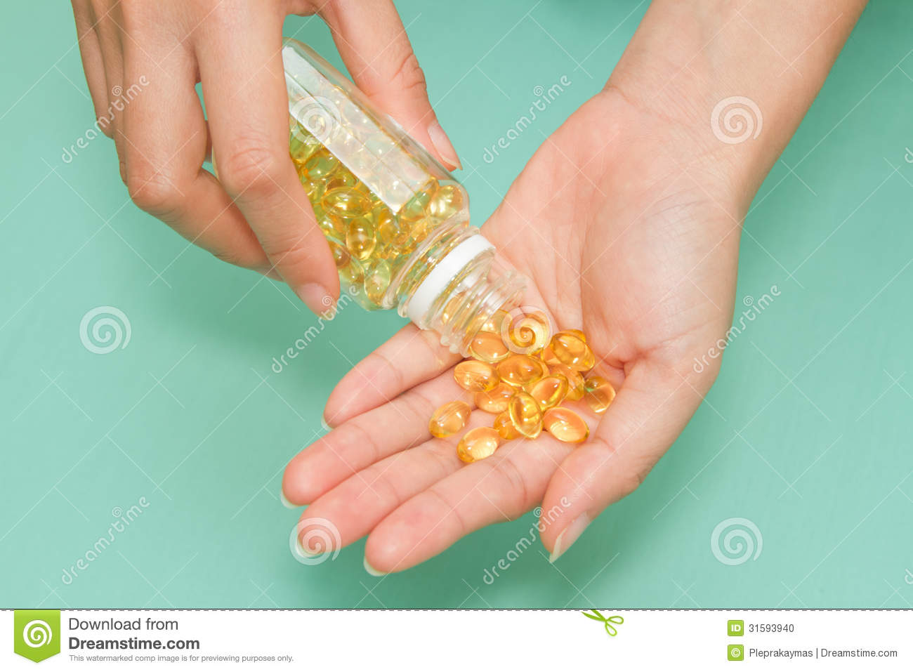 Hand with yellow omega health oil capsule stock image for Best time to take fish oil