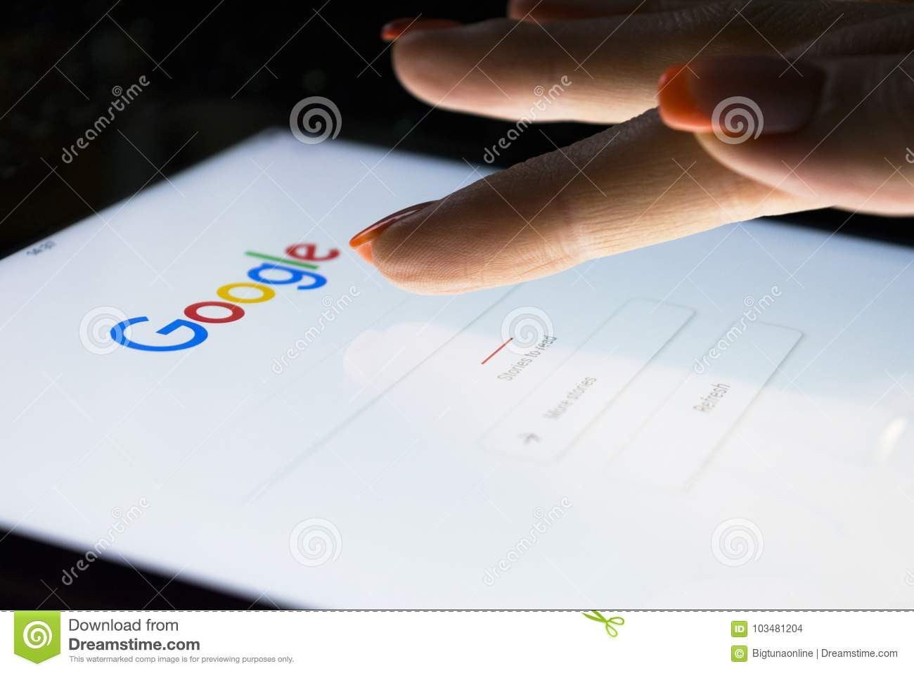 A woman`s hand is touching screen on tablet computer iPad Pro at night for searching on Google search engine. Google is the most