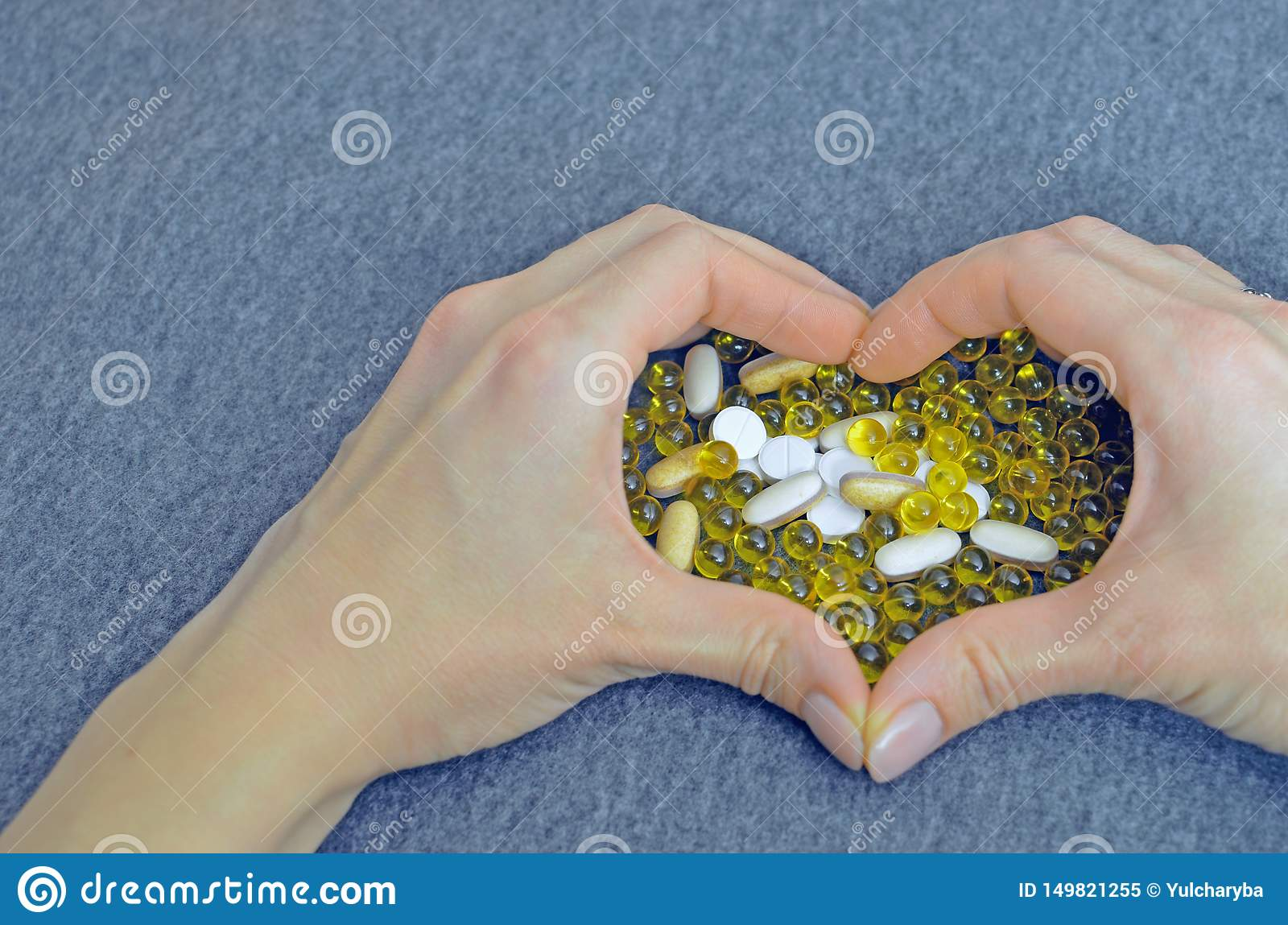 Woman`s hands created a heart shape. White and yellow pills. Mock up for special offers as advertising. Medical and