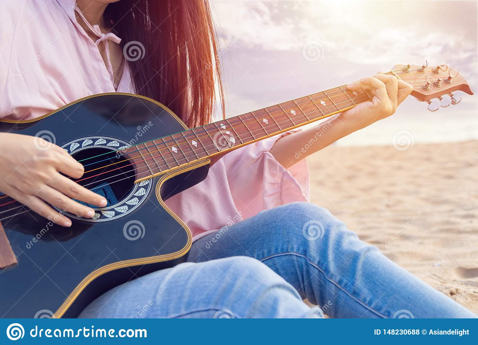 Woman`s hands playing acoustic guitar, capture chords by finger on sandy beach at sunset time. playing music concept