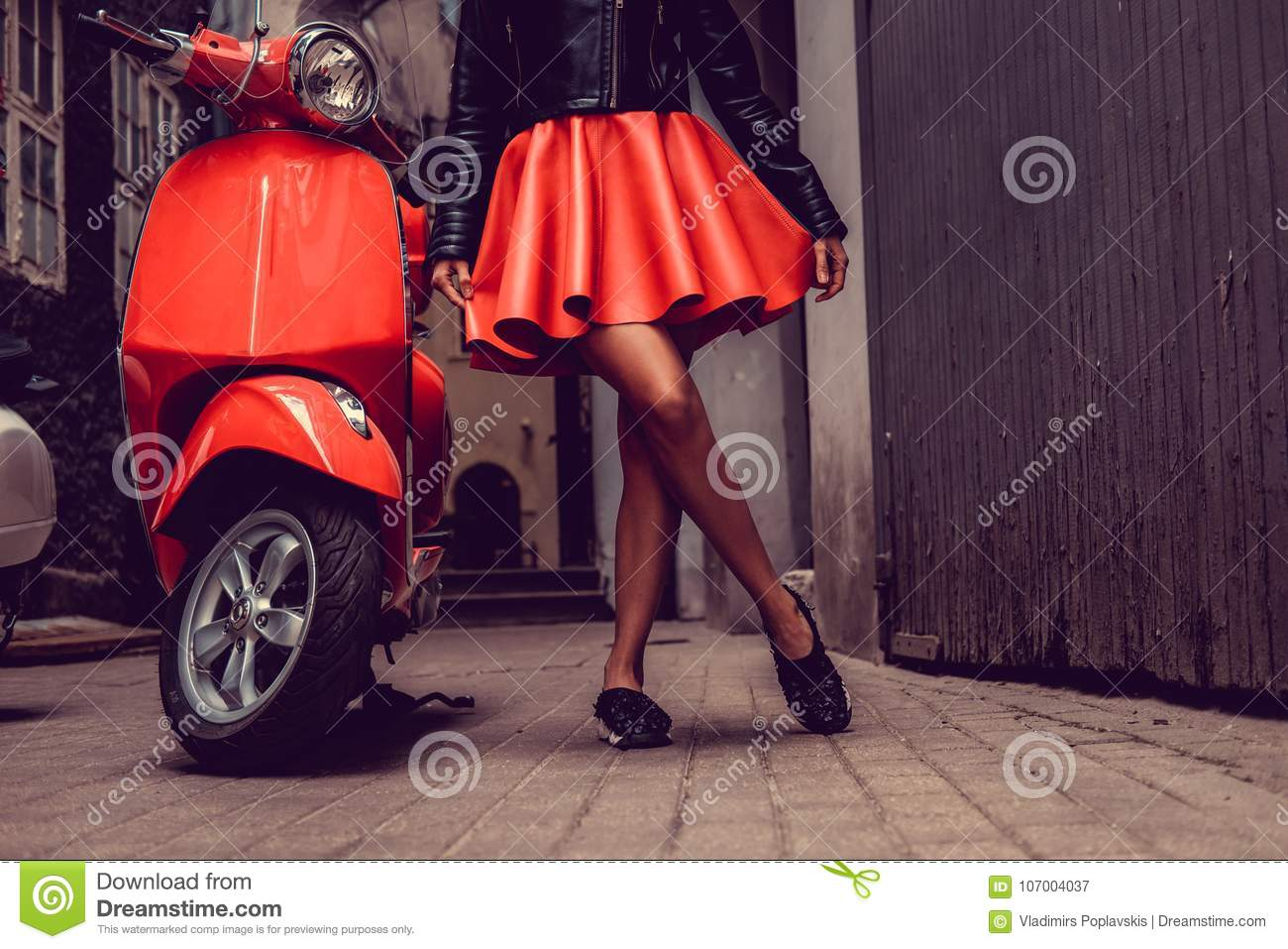 Woman`s legs near red motor scooter.