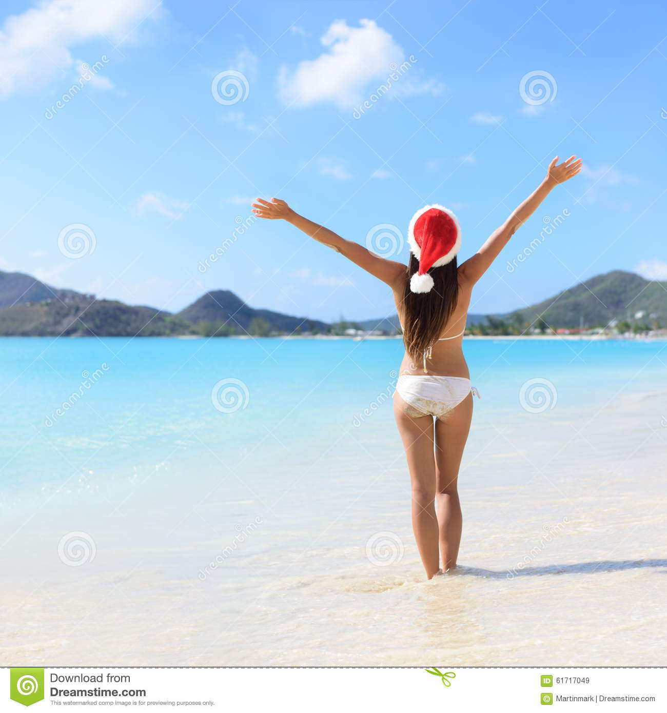 f1dddb4635b Woman standing in water with arms outstretched at beach. Rear view of female  is wearing Santa hat and bikini. Carefree tourist is enjoying Christmas ...