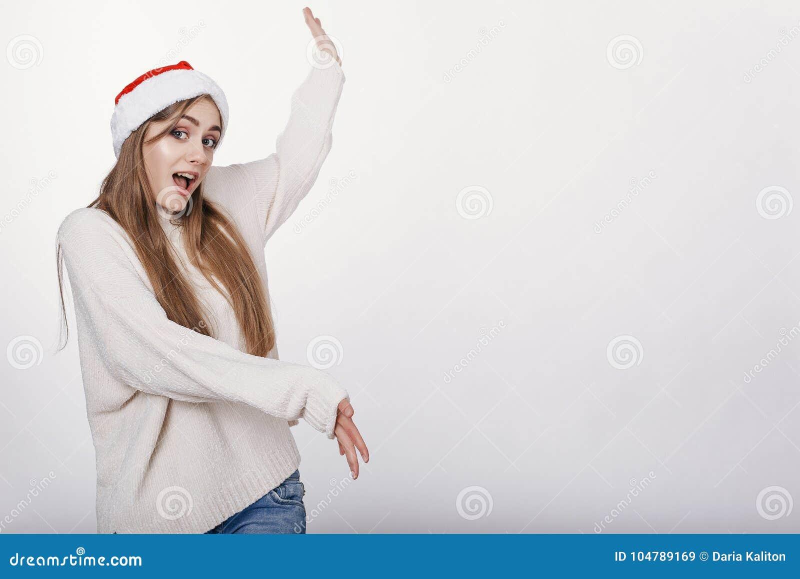 Woman in santa hat pointing on something big