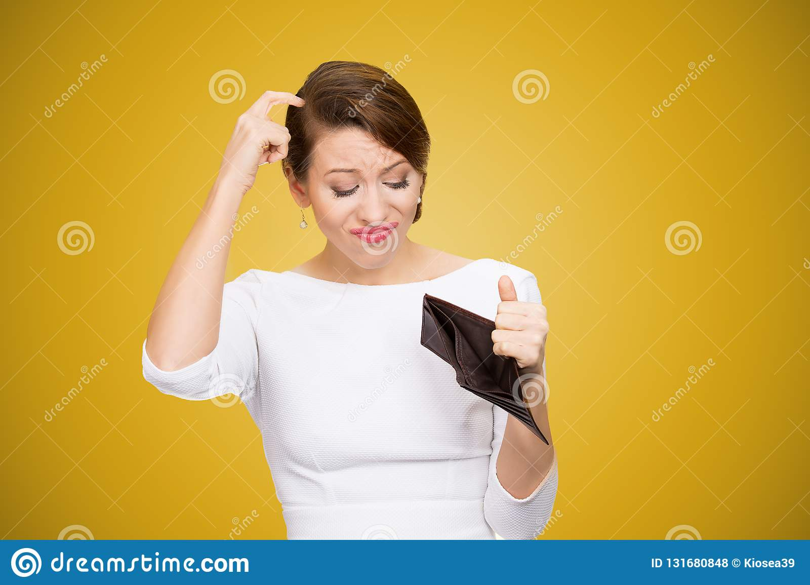 Woman scratching in head and looking inside of empty wallet having no money