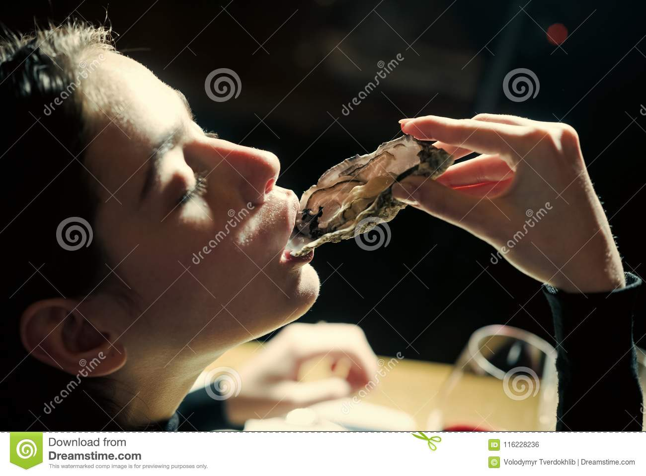 Woman In Seafood Restaurant Tasting Fresh Oysters  Stock
