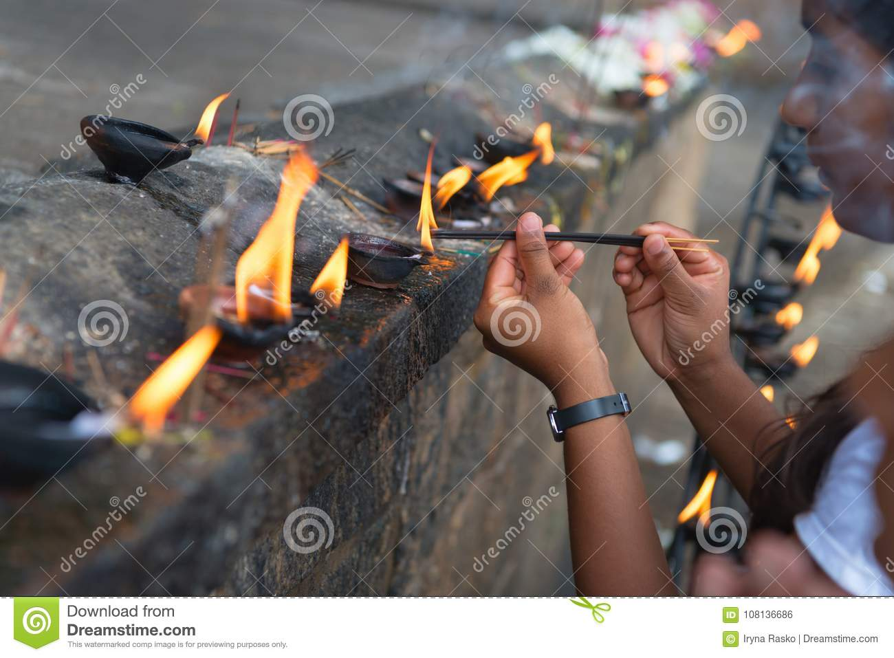 Woman sets fire to fragrant sticks in the temple offerings place