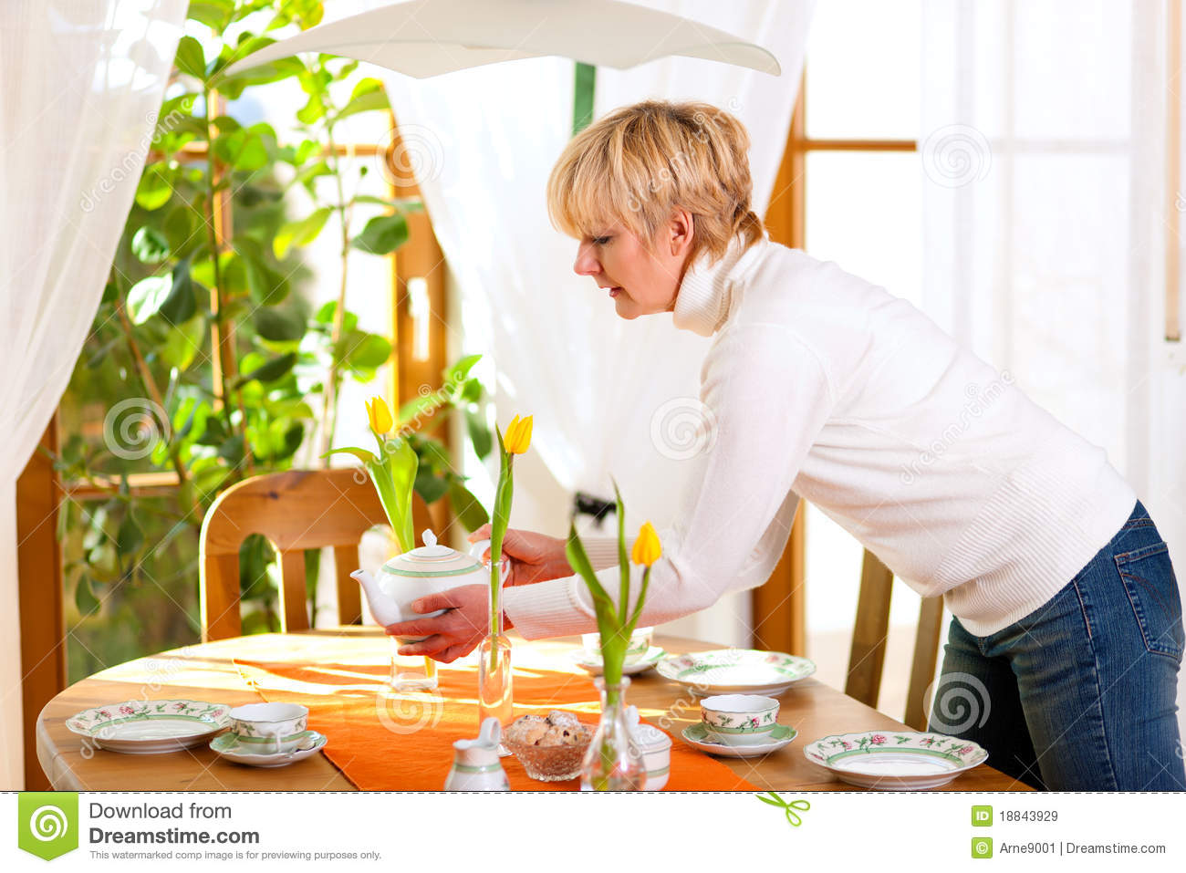woman setting the table for tea of coffee time royalty