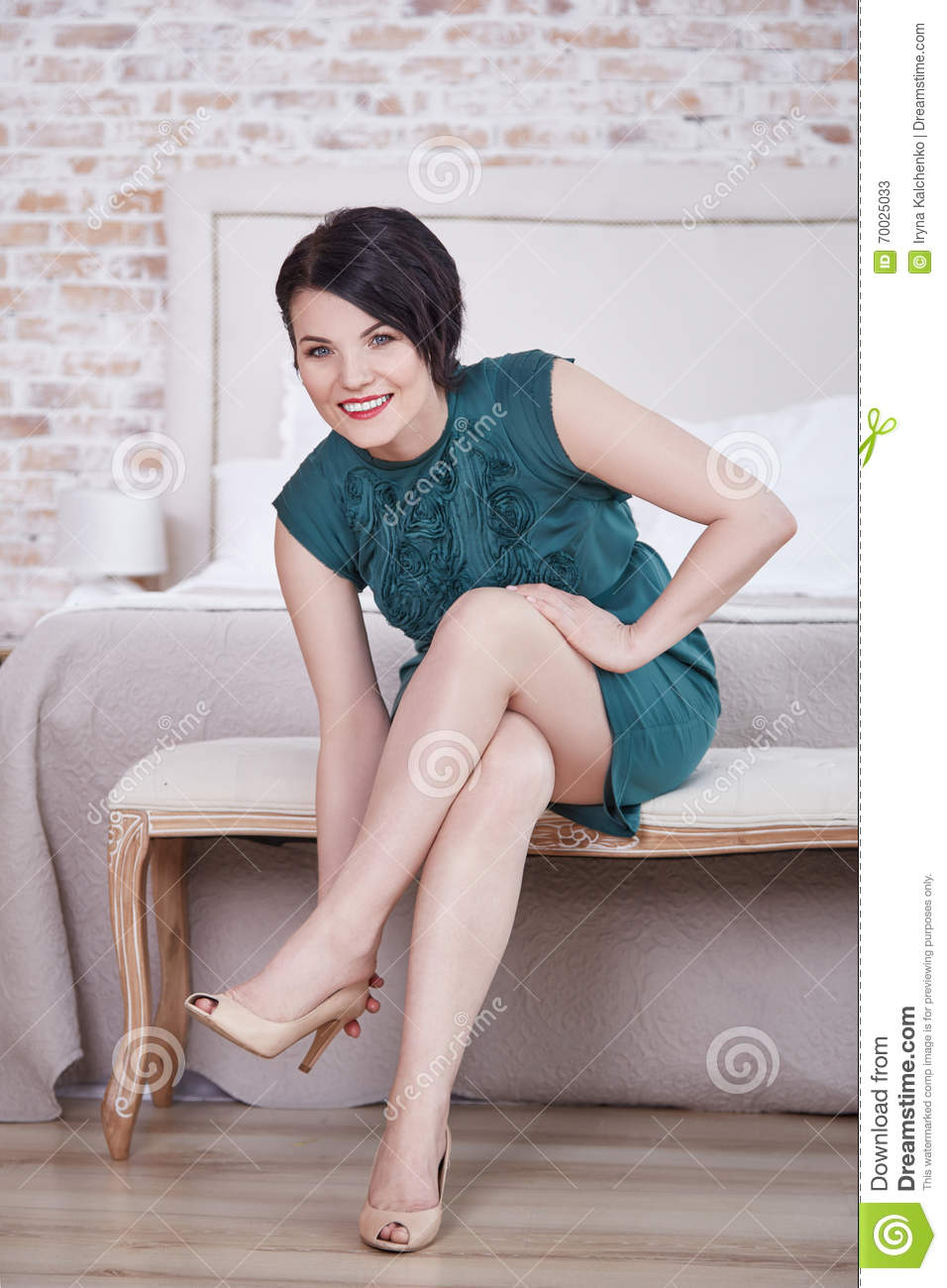 Beautiful woman brunette hair natural makeup wear short silk green dress high heels shoes sit on chair in interior bedroom home housewife light loft design ...