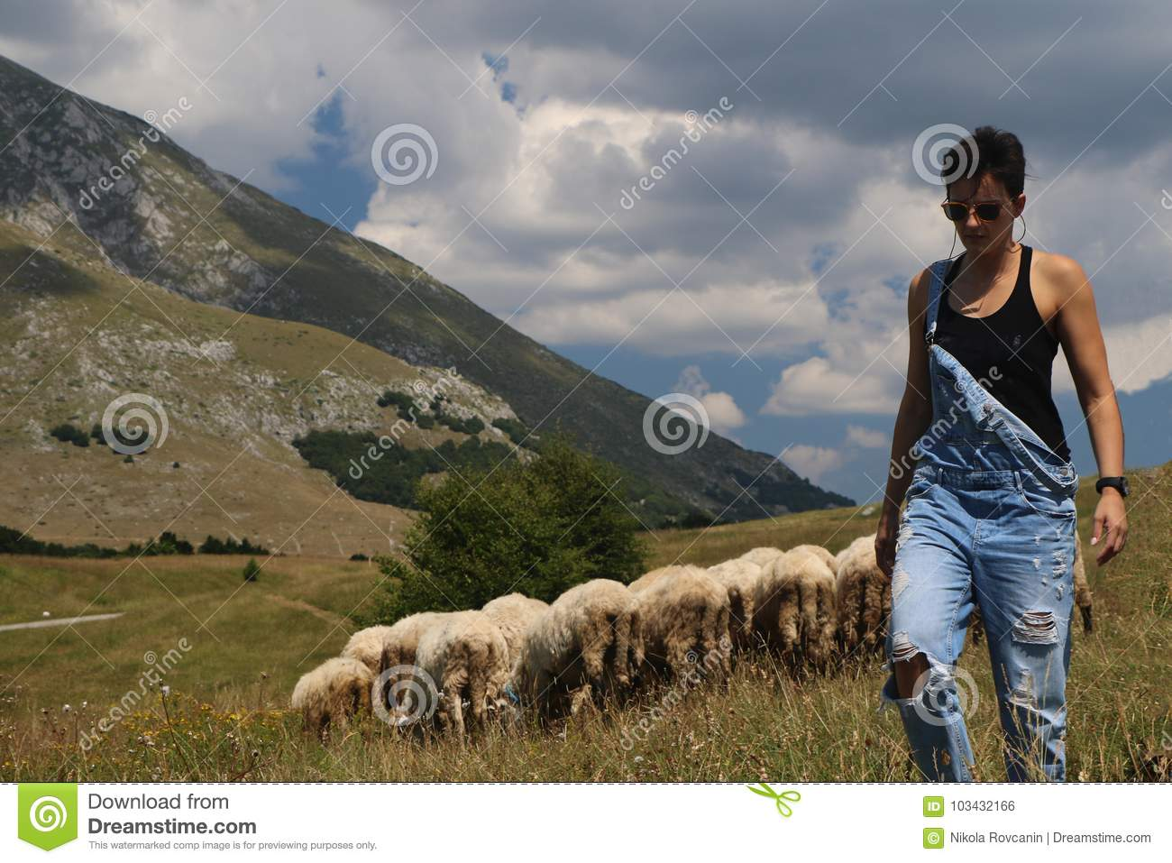 Woman with sheeps in the background
