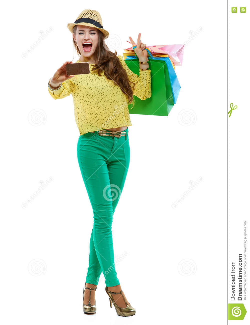 Woman with shopping bags showing victory and taking selfie