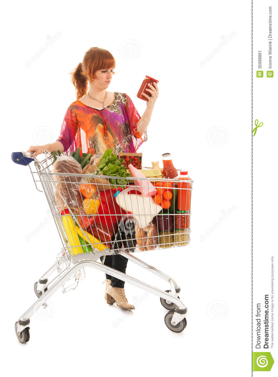 Woman with shopping cart full with dairy grocery products reading ...