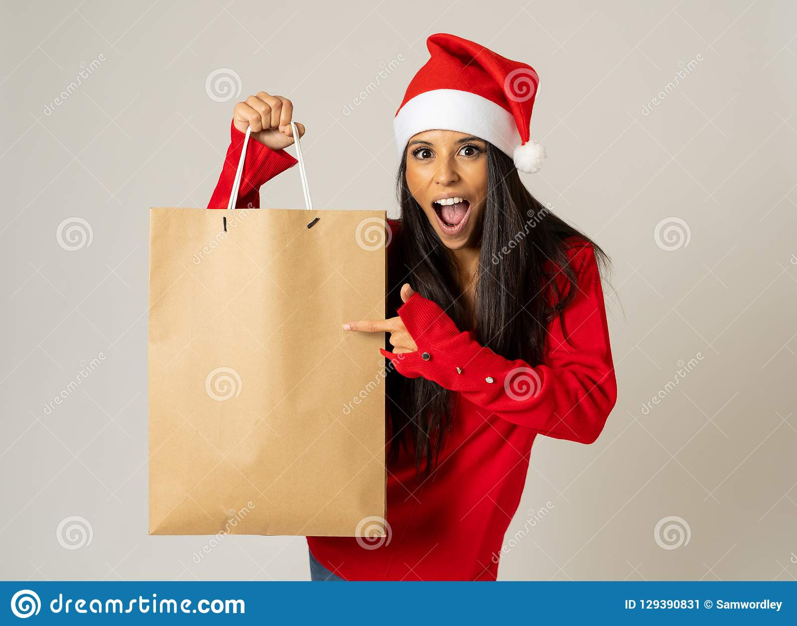 Woman shopping for christmas gifts with shopping bags and santa hat looking excited and happy