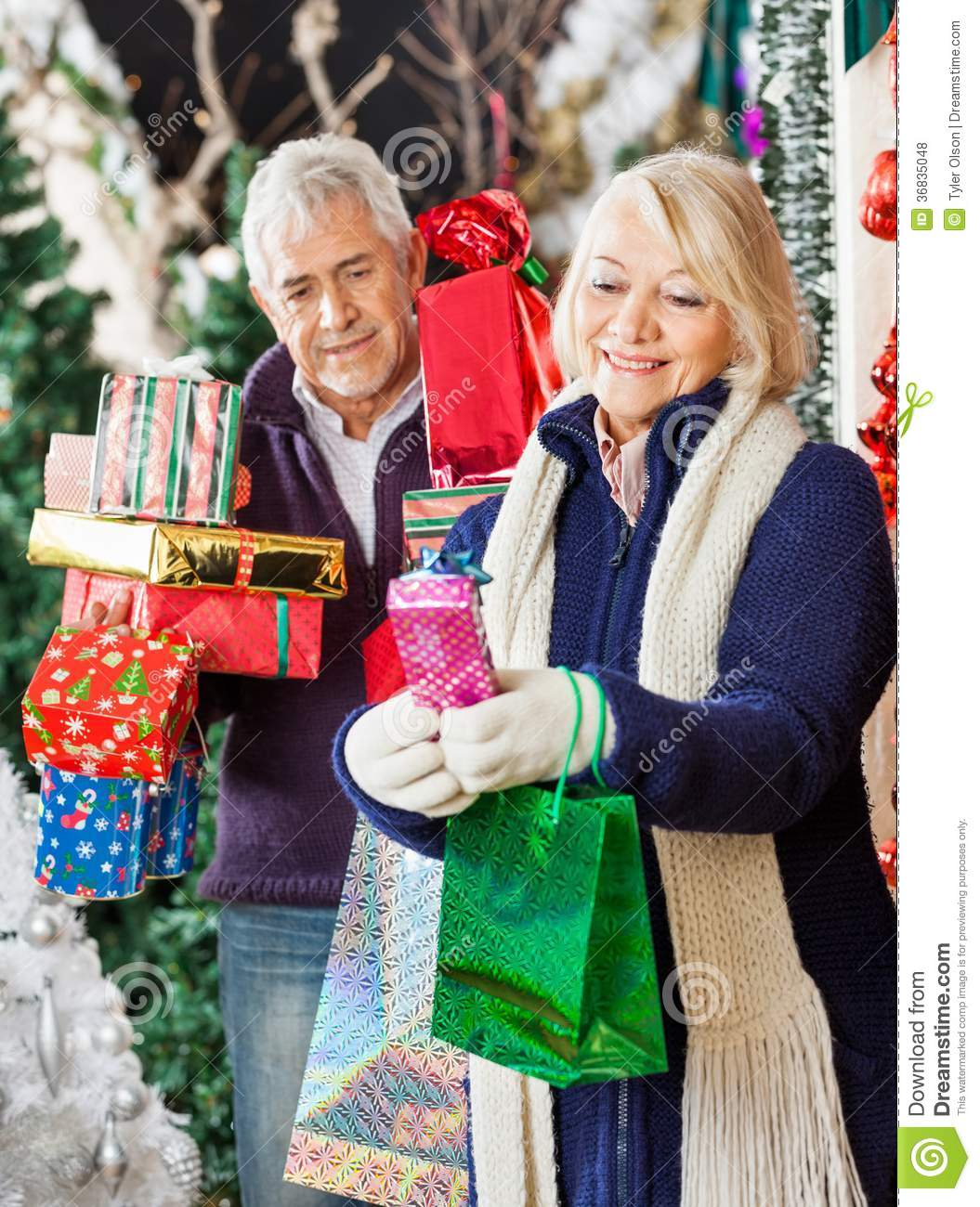 Woman Shopping Christmas Presents With Man Royalty Free