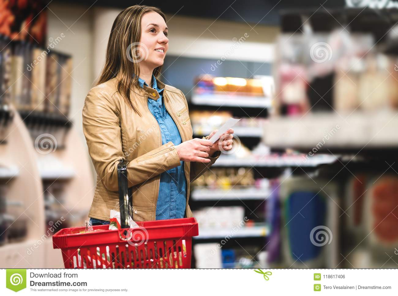 woman with shopping list in supermarket and grocery store stock