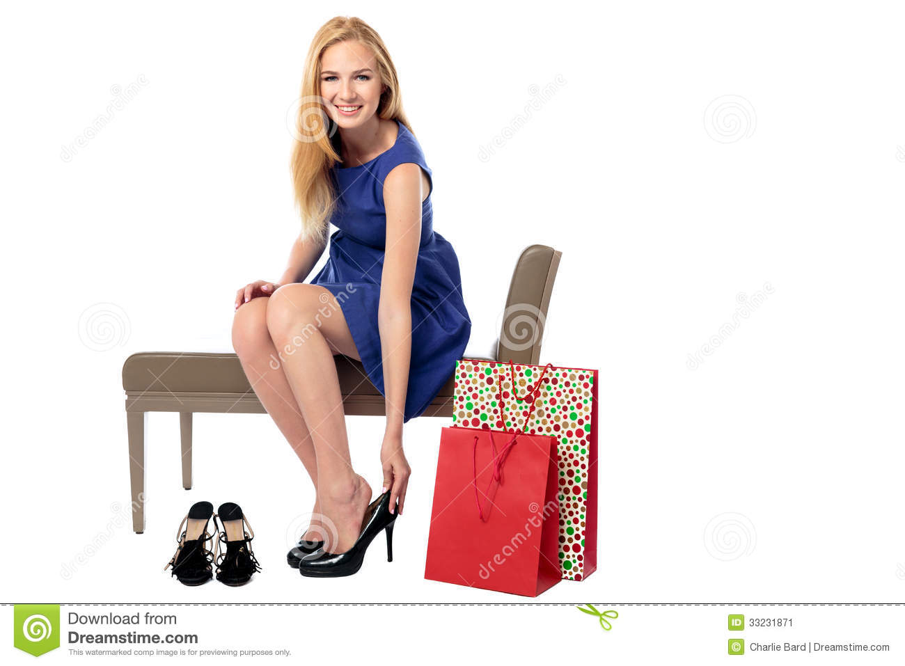 caf6520cc868e Smiling stylish young woman shopping for shoes sitting on a bench trying on  a pair of elegant stilettoes with carrier bags propped alongside, on white