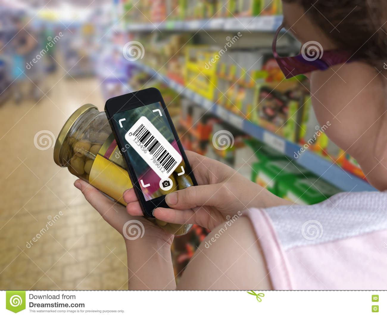 Woman is shopping in supermarket and scanning barcode with smartphone in grocery store.