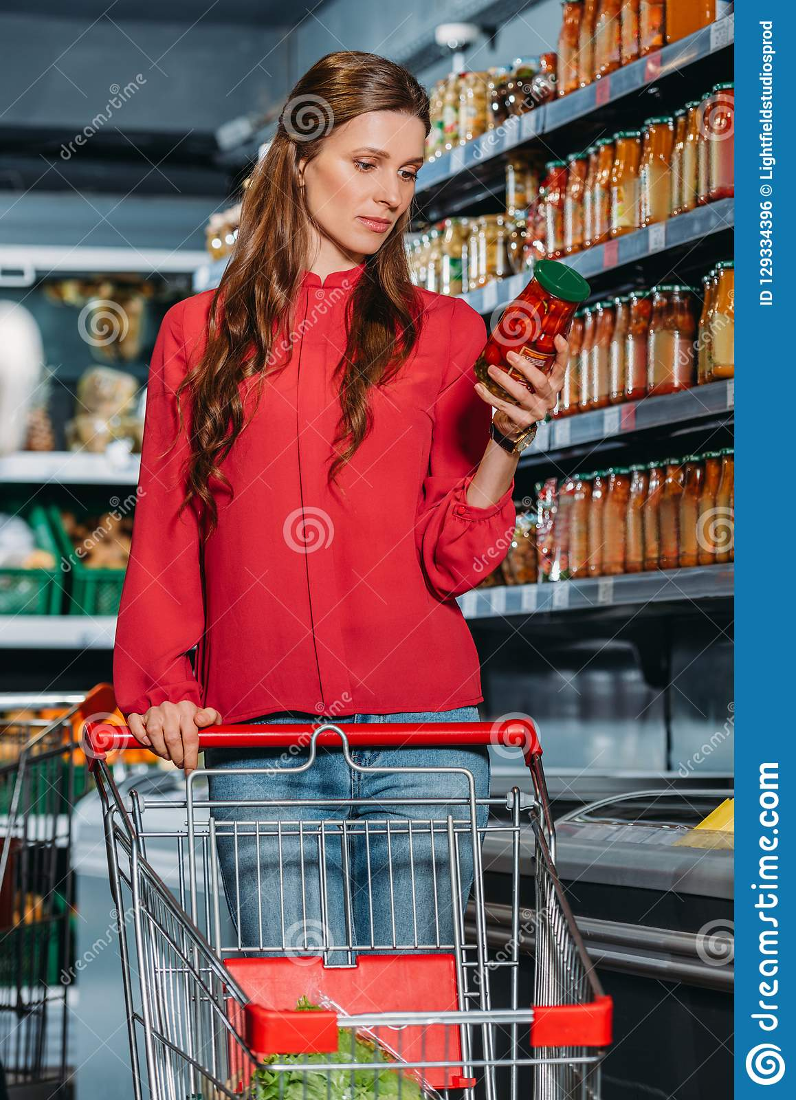 woman with shopping trolley choosing products