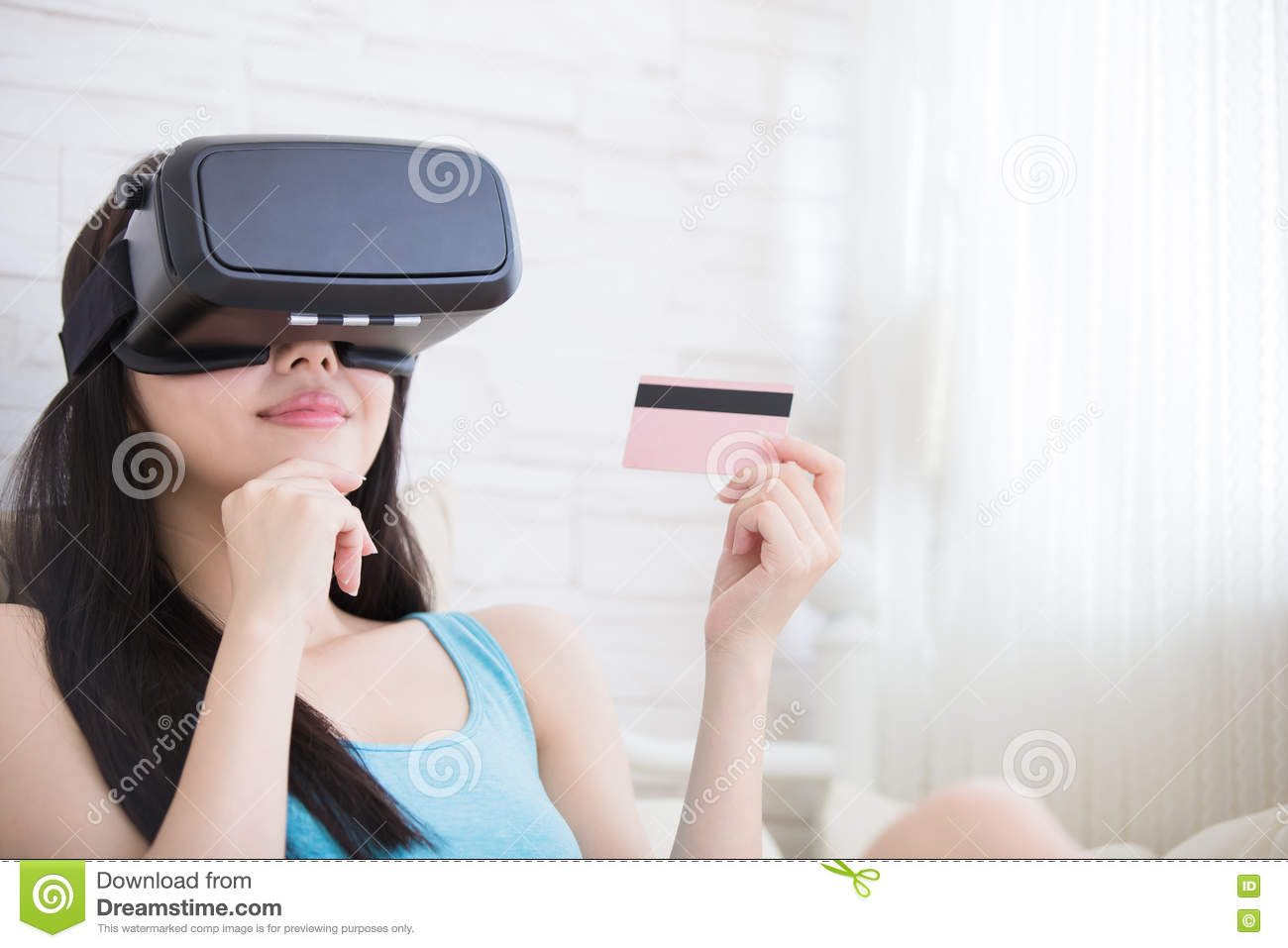 7b789d5e22 Smile happy woman shopping online by VR headset glasses of virtual reality  at home