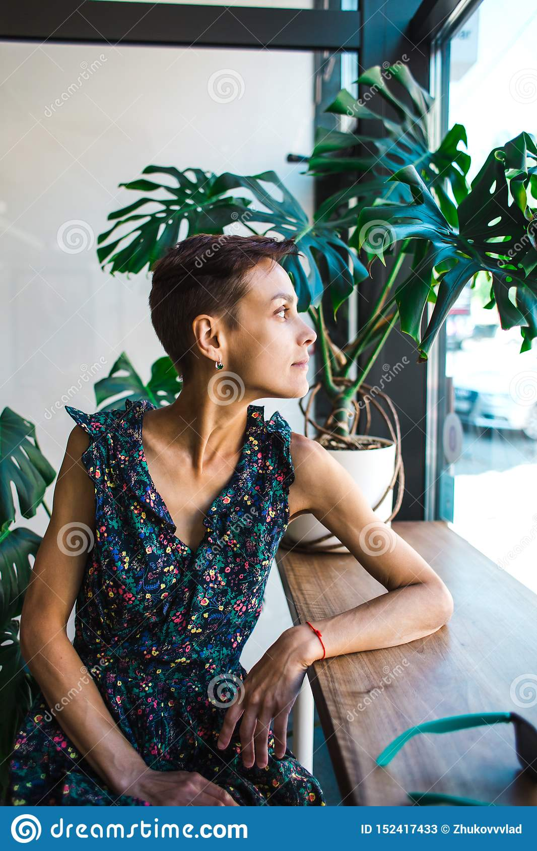 A woman with short hair dreamily looks out the window