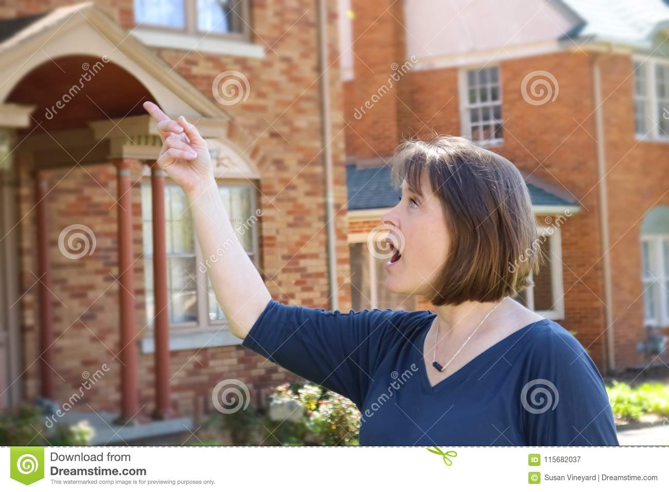 Woman with short hair in front of blurred brick houses points and looks surprised