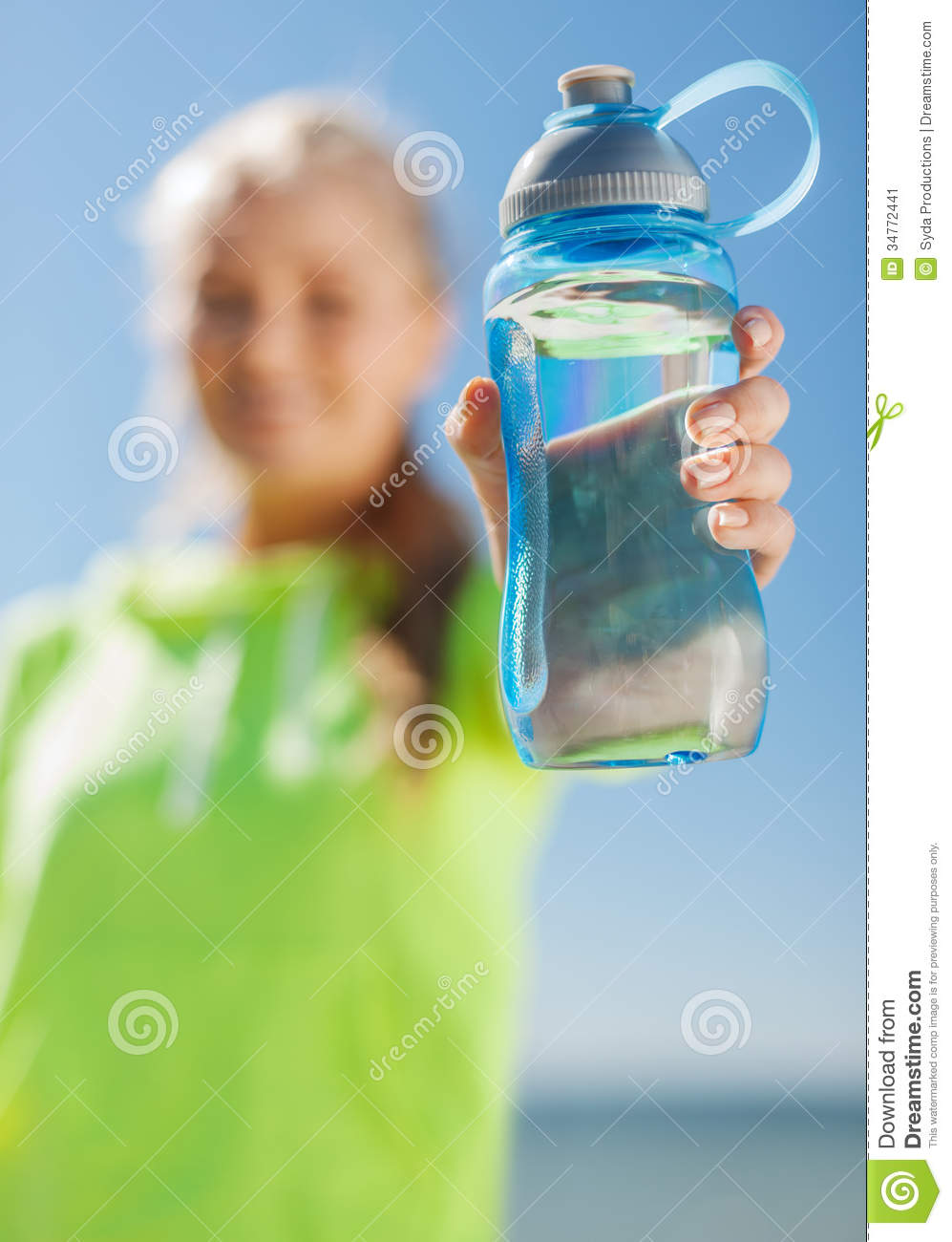 Lifestyle concept woman showing a bottle of water after doing sports