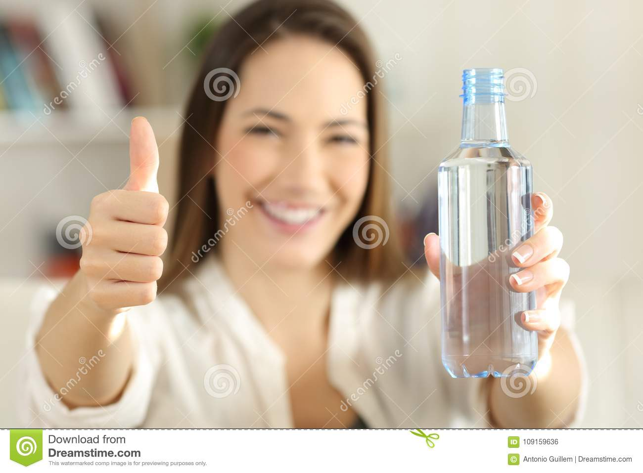 Woman showing a bottle of water with thumbs up