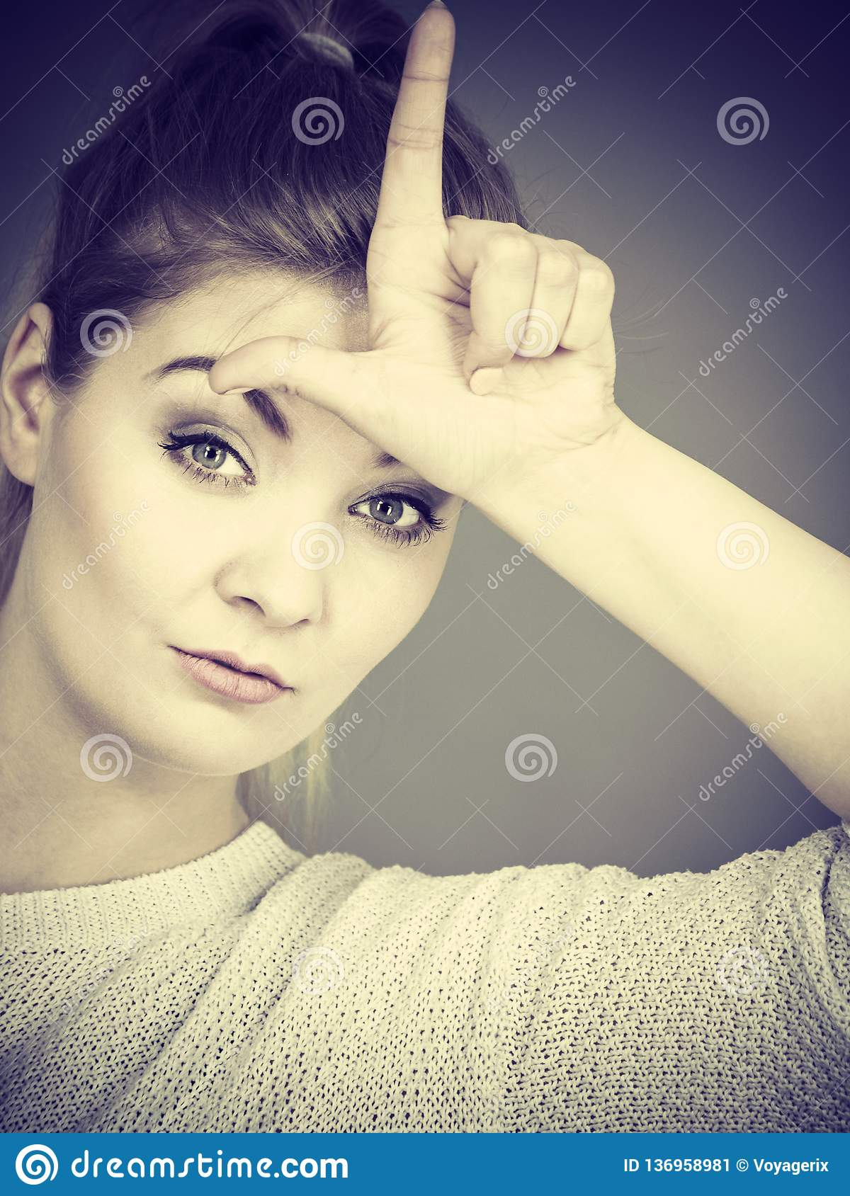 Woman Showing Loser Gesture With L On Forehead Stock Image