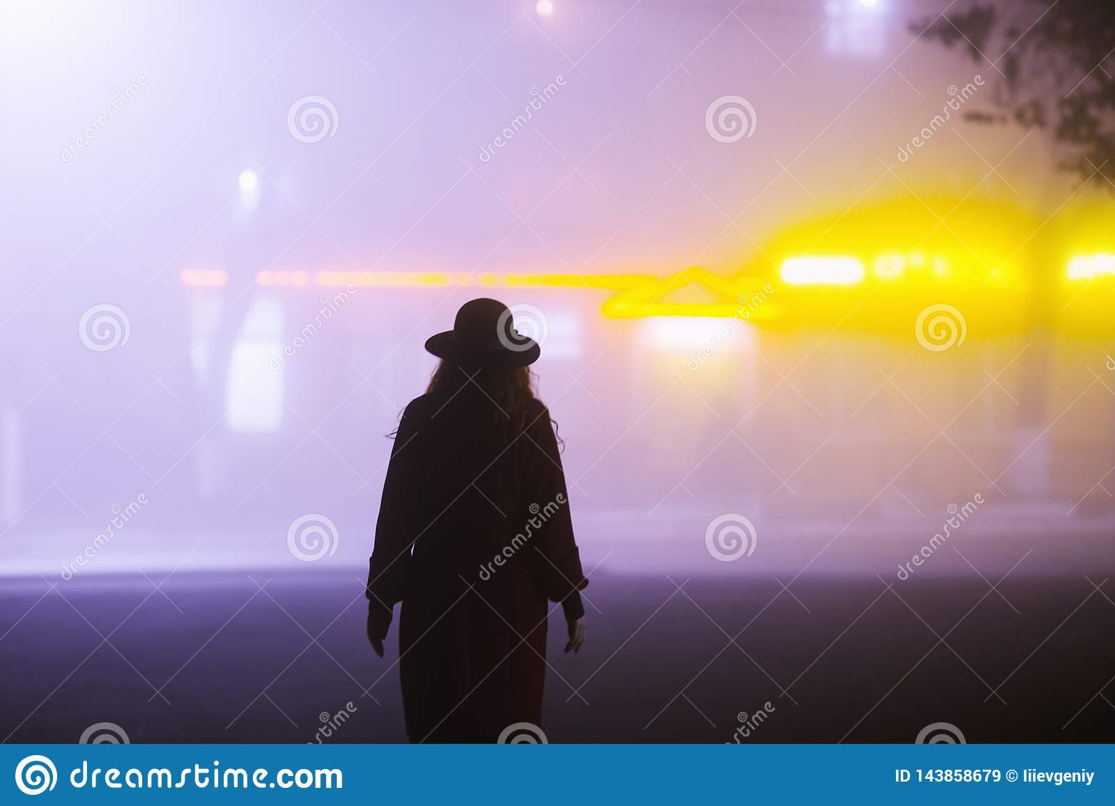 Woman silhouette on background of the night city in fog. Thick mist in dark scary evening city. Dark noir silhouette in hat on