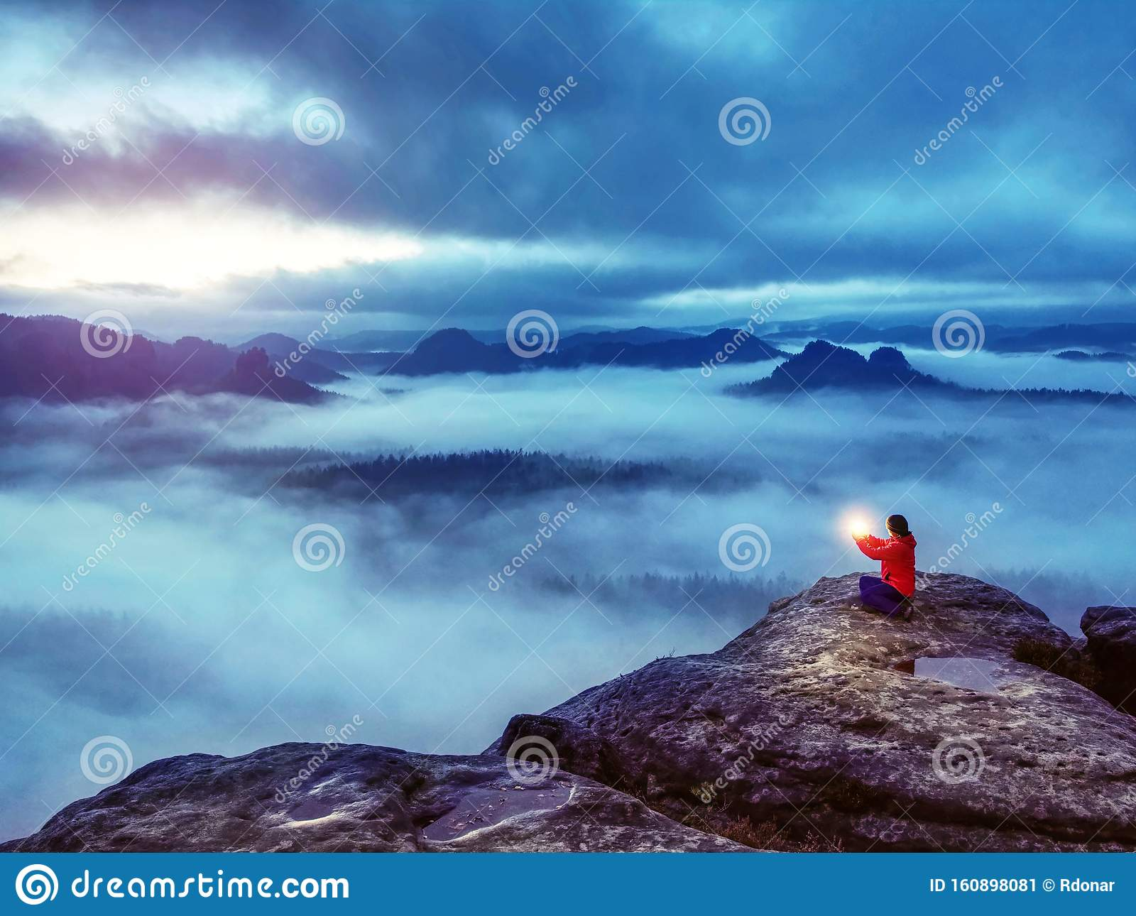 Woman sit on summit in hands holding flash bolb. Girl waiting