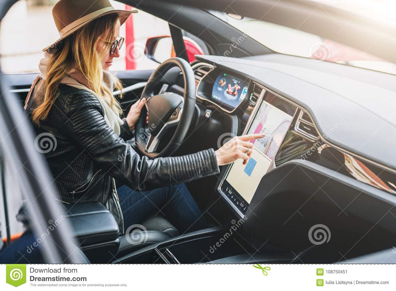 Woman sits behind wheel in car and uses electronic dashboard. Girl traveler looking for way through navigation system.