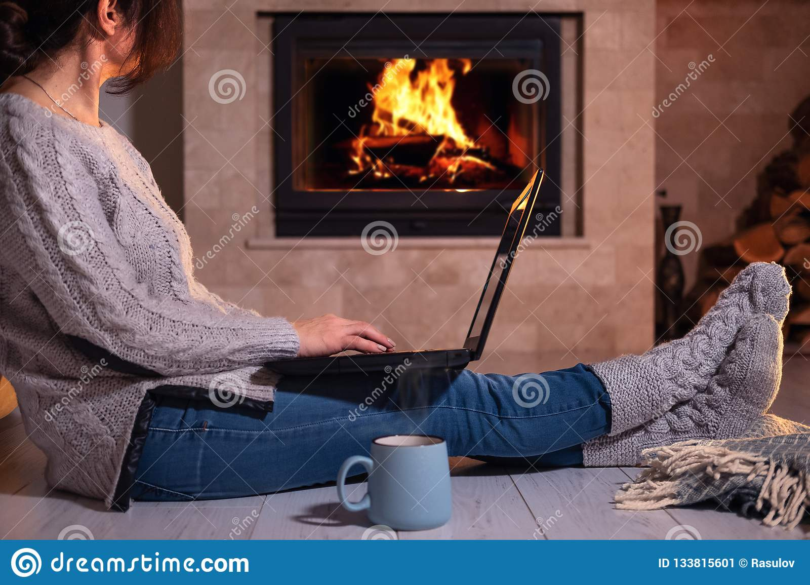 Woman sits at the floor with a laptop on the fireplace background.