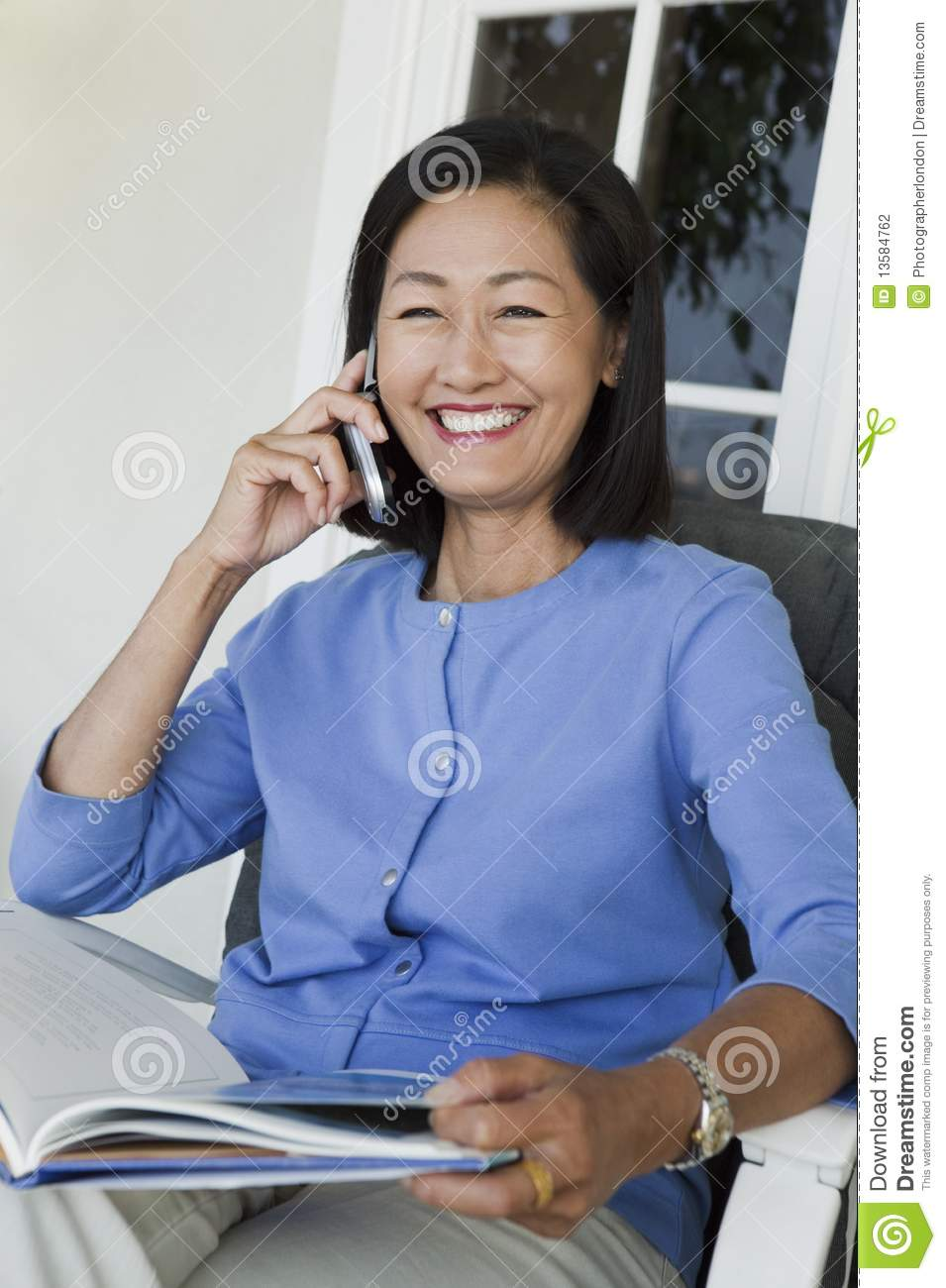 Woman sitting on armchair, talking on mobile