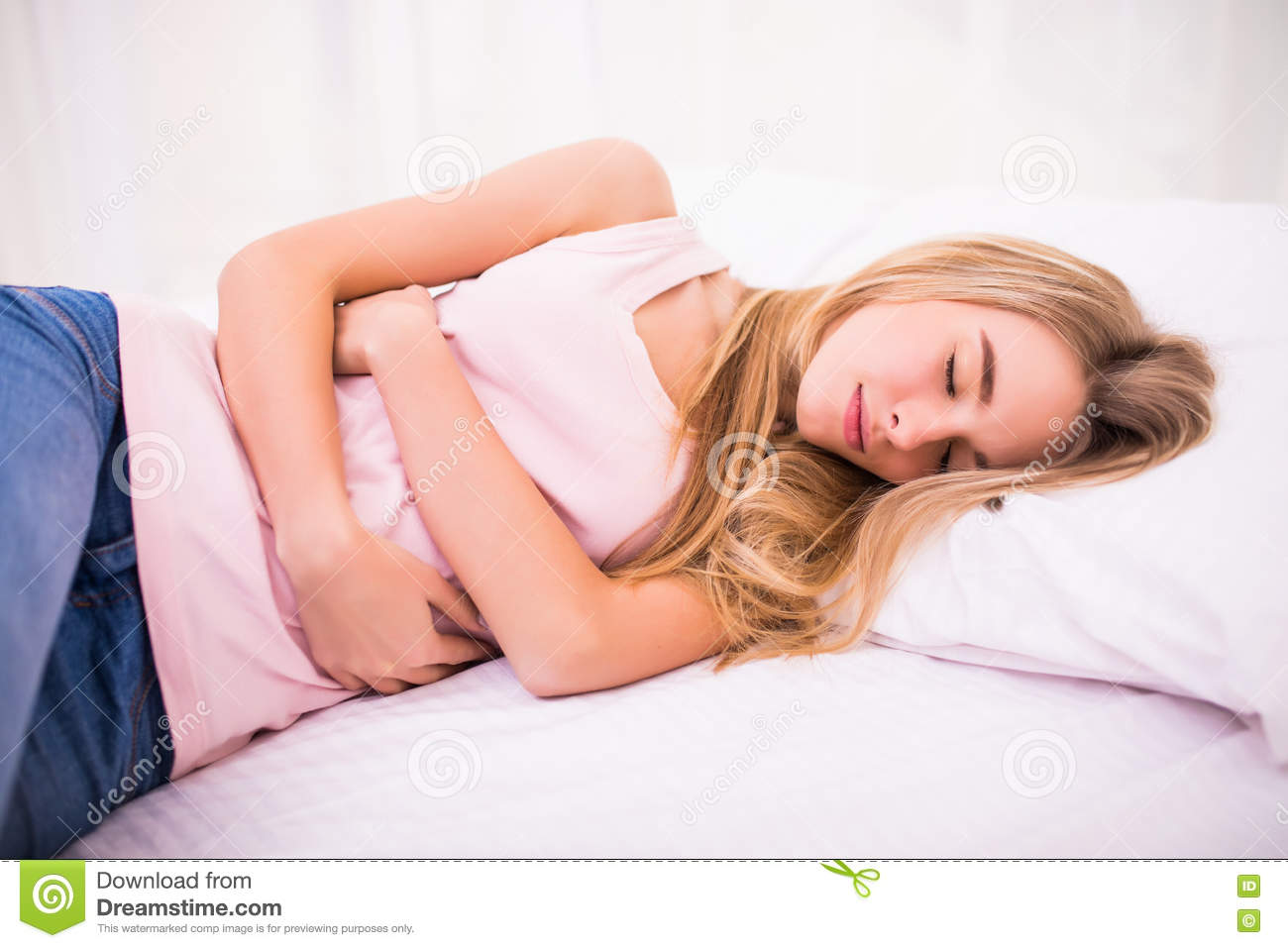 Woman sitting on bed and suffering from abdominal pain